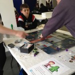 Izaak playing HeroClix with Rory from The Creativity Hub